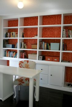Use same fabric for back of bookcase as for curtains.  Orange something?