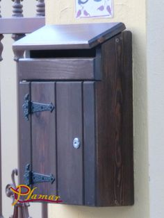Buzón de madera diseño rústico, con grandes cierres en la puerta frontal y una gran ranura superior.