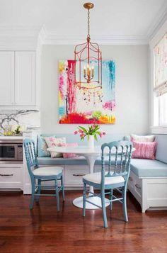 coin repas d'angle moderne en couleurs pastel avec une banquette d'angle avec rangements et un tableau d'art contemporain en couleurs vives