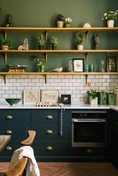 Green interiors are very in style right now and we love it, these Ho Ho Green walls by Little Greene look perfect paired with our Pantry Blue cupboards and classic metro tiles. The wooden open shelves were a great decision, they provide lots of kitchen storage while keeping the space feeling light and airy. #deVOLKitchens #OpenShelves #SubwayTiles #PantryBlue