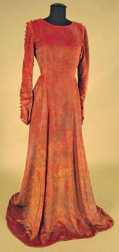 velvet gown and purse, 1920. Persimmon orange silk velvet stenciled all over in metallic gold and silver ginko leaves, long sleeves with open seam trimmed with gold baubles, shoulder seam trimmed with coral glass beads, matching small drawstring purse.