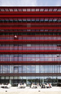 CocaCola Headquarters in Berlin by NPS Tchoban Voss, Berlin, Germany - The water façade to the south is fully glazed; in front is a gallery-like balcony spanning the width of the building and faced with a structure that serves as a fixed sunscreen, comprising slim, vertically S-shaped profiles and horizontal beams at different spacing. The three other façades are divided by short strip windows, switching positions at each level, and are clad in glazed ceramic elements in various red tones.