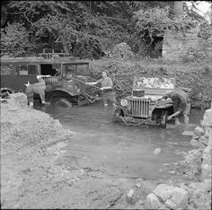 A jeep and a CMP truck being washed in a stream, 5 July 1944.