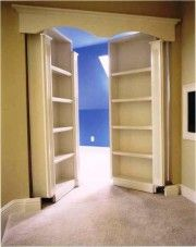 Two shelves on wheels that reveal a hidden room behind.