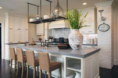 source: Wolfe Rizor Interiors  Lovely cottage kitchen with white floor to ceiling kitchen cabinets, white kitchen island, gray quartz countertops, sink in kitchen island, marble slab backsplash, woven bar stools and white brick walls.