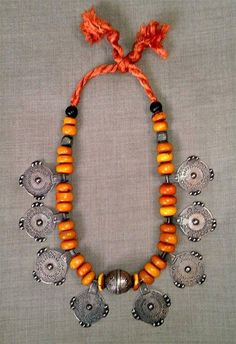 Posted by Jamey Allen in ETHNOGRAPHIC GROUP. His caption: This is an original Moroccan Berber necklace of Baltic amber beads with eight circular silver pendants, and a central ellipsoidal silver bead.   Region of origin Tata.