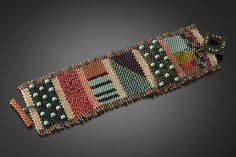 Mixy Cuff in Peach and Olive by Julie Powell. Using just a needle and monofilament thread, the artist weaves tiny glass seed beads one by one into a dense, flexible fabric rich with detail and color. Hand-beaded toggle closure. Limited quantity of 25.