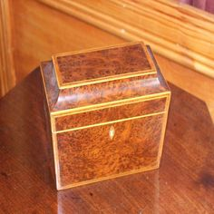 A yew wood rectangular tea caddy, English, circa 1820. 15 cm high, 20 cm wide from Carter's Price Guide to Antiques