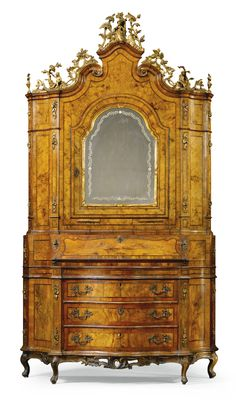 An Italian walnut and parcel-gilt bureau cabinet, Venetian mid 18th century the scrolled cresting surmounted by a carved female figure in 18th century costume and a building amongst trees flanked by flowers, foliage and scrolls above an arched cupboard door with a mirror opening to reveal a fitted interior with five pigeon holes above a central door flanked by two further recesses above two short drawers and three further short drawers