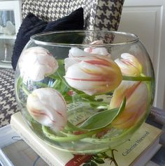 Tulips in a Fish Bowl Photo by Karen Kirk. Buy tulips not yet open. Remove some leaves & lay on the counter out of water. In an hour or so the stems  become limp & pliable so you can bend them easily inside the bowl. Fill the bowl with about two or three inches of water & add floral food. Once the tulip stems are limp enough to bend, clip the stems on a diagonal & shape one tulip at a time inside the bowl. Make sure the end of each stem is submerged in water. Stagger the tulips as shown.