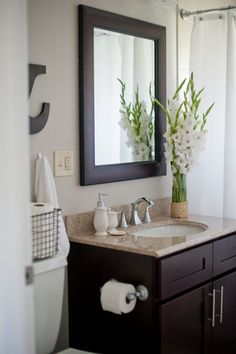 """Fresh flowers and white bathroom accessories help create a """"spa-like"""" feel right in your own bathroom! #HomeGoods #HappyByDesign #sponsored"""