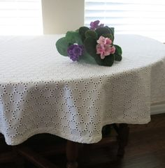 Here is a round white eyelet tablecloth perfect for entertaining at showers and weddings. It is in very good used vintage condition with no holes and just a few light discolorations. Since it is white they can be treated with bleach.  The round tablecloth measures 58 inches round and has a sewn in hem at the edge. There is a tag that says it is machine washable.