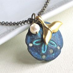 Sand Dollar Necklace -  Gold Whale Tail, Patina, Pearl,  Brass, Ocean Jewelry, Beach Jewelry. $29.00, via Etsy.