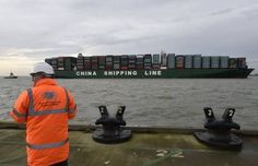 A port official watches as the CSCL Globe docks at the port of Felixstowe