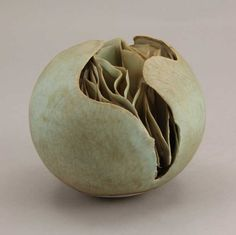 Peter Simpson |  A 'Split' Form, circa 1974.    Porcelain, the spherical body split open to reveal fine undulating fins within, mottled green crackle glaze