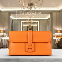 Hermes Orange Jige 21cm Clutch in Swift Leather | Available Now For inquiries, please contact sales@shayyaka.com or +961 71 594 777 (Call, SMS, WhatsApp, or iMessage) or Direct Message on Instagram (@Shayyaka). Guaranteed 100% Authentic | Worldwide Shipping | Bank Transfer
