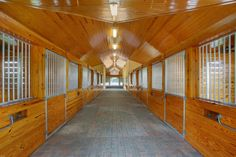 This barn in Wellington, FL, features double-walled stall fronts, concealing plumbing that delivers water to each stall. Faucet handles are recessed into the wall on the aisle side, while the spouts face into the stalls where the buckets hang.