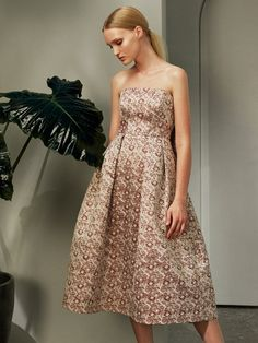 Erdem looks to the glamour for the 1940s for Pre-AW17 inspiration. This pale pink and rich burgundy floral satin-jacquard Alina dress is crafted to a strapless silhouette, and turns to reveal to deep box pleats that create a cocooning cape-like layer. Ensure a modern finish with a simple clutch and block-heeled mules.