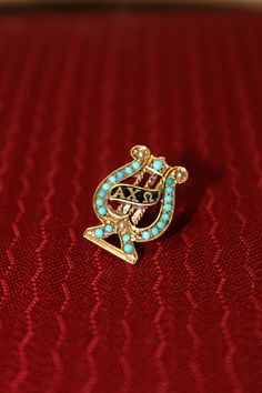 Badge set with pearls and turquoise stones. Prior to early 1900s. www.alphachiomega.org