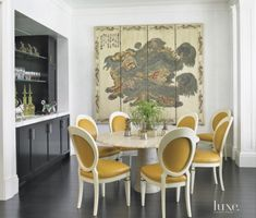 Classic Eclipse side chairs, from Bunny Williams Home, encircle the limestone table in the dining room. Edelman Leather's Royal Hide in Sun Baked picks up the butterscotch accents in the Chinese Coromandel screen, which was found for the owner by Angelo Donghia.