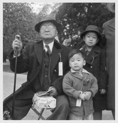 """May 8, 1942. Hayward, CA. Original caption: """"Grandfather and grandchildren awaiting evacuation bus. The grandfather conducted a dyeing and cleaning business. The family unit is preserved during the evacuation and at War Relocation Authority centers where evacuees of Japanese ancestry will be housed for the duration"""" Most of the photographs were taken by WRA photographers for publicity purposes and tend to show people who are smiling or stoic. Captions emphasize humane treatment."""