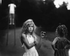Candy Cigarette, 1969 by Sally Mann  Sally Mann's famed body of work Immediate Family documents her three children, Emmett, Jessie and Virginia, in an array of scenes at their home in the foothills of the Blue Ridge Mountains in Virginia. Capturing them as they sleep, interact, dress up and role play. Mrs. Mann's photographs highlight a heightened maturity that defies their age, creating a tension between the push of childhood and the pull of adulthood. Even when the scenes themselves are…