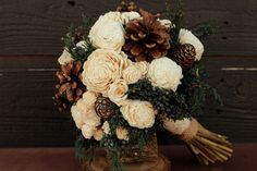 What better rustic element for a winter wedding than the pinecone? By combining a few with porcelain white tea roses and greenery, this bouquet was made for a woodland affair in the snow.