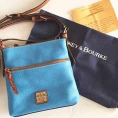 AUTHENTIC DOONEY AND BURKE LEATHER CROSSBODY NWOT. LEATHER LETTER CARRIER WITH DUSTBAG AND REGISTRATION CARD. 23.5 to 27.5 inch strap drop. The strap comes apart to convert from CROSSBODY to short shoulder.  Sky blue color. Dooney & Bourke Bags Crossbody Bags