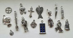 This is a set of charms inspired by the television phenomena Dr. Who. The set includes one of each: Silver and blue enamel Tardis (27mm), gas mask (28mm), Roman helmet (15mm) and sword (25mm), gear (15mm), weeping angel wings (30mm), sunflower (10mm), rose (17mm), scarf (25mm), a trench coat (22mm), fedora (16mm) and umbrella (34mm), an astronaut (30mm), Big Ben (25mm), a Dalek (15mm) and a Sonic Screwdriver (40mm). Thank you for looking