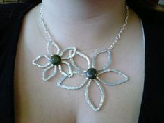 Hammered aluminum wire formed into a pair of flowers with semi precious stone centres.
