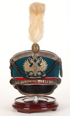 AN IMPERIAL RUSSIAN OFFICER'S SHAKO OR KIVER FOR AN AIDE DE CAMP. Model 1907 'Bell crown' shako with black leather top, royal blue wool rise and red band, piped in white, and black leather visor, with silvered eagle plate, chin scales and visor trim, as well as a cockade and horsehair plume. Complete with silver bullion crown braid and cords. Lined in black fabric and leather sweatband. - Jackson's International Auctioneers and Appraisers
