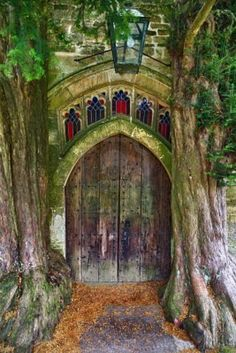 England...The wooden door of St Edwards church, with 2 ancient yew trees, Stow-on-the-Wold in the Cotswolds...