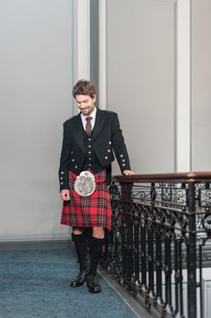 The Heritage Collection: The Red Mackenzie tartan kilt is styled here with matching clan crest accessories and a traditional Prince Charlie jacket and waistcoat.