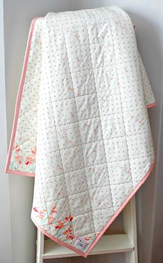 This Handmade Coral Nursery Whole Cloth Baby Quilt features an allover Navy and Coral print with an adorable floral trim in coral with a creamy minky cuddle dot on the reverse. Plus an all over diamond quilting pattern. Such a super cozy quilt for your baby or toddler. This is a great size to place on the floor for babys tummy time, drape over the crib or use on your toddler's bed. You and your kiddo will love to snuggle in this Minky backed quilt!  Little b Cotton Shoppe Quilts are…