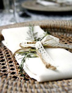 déco mariage champêtre - sous-assiette en osier, serviette blanche décorée d'une branchette verte et fine et un ruban en dentelle