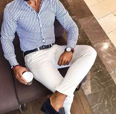 The stripes are what strike me about the outfit. Small thin stripes of a kind of denim blue. The fit of the shirt is perfect -- it's been tailored. Like black belt, and pure white pants.