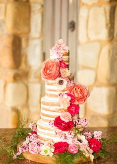 Naked cake with magenta, peach and pink flowers cascading down the side ~ we ❤ this! moncheribridals.com
