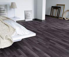 Black vinyl flooring in a wood-grain pattern is gorgeous in this modern bedroom. (Basement)