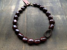 Dark brown flat oval seeds with a golden crochet sparkle for this necklace