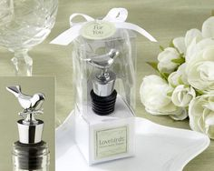 "Love Birds Wedding Wine Bottle Stopper made of chrome.  It features a long conical base wrapped with a black rubber gasket for a tight seal. The top of the stopper has a tiny bird sitting atop a branch. It comes packaged in a clear gift box with a base design featuring a cutout tree with heart shaped leaves. The top of the box is decorated with a white bow and a ""For You"" tag."