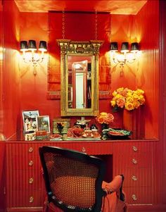 Bold and Theatrical Interior Design by Mary McDonald - House Beautiful. The glamorous red dressing room is part of a large walk-in closet in the master bedroom. A 19th-century Regency mirror hangs from the ceiling on chandelier chains.