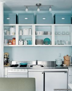 Everyday inspiration for keeping your kitchen clutter-free, plus Martha Stewart's own kitchen organizing ideas.An editor's tiny apartment still manages big style and a clutter-free appearance. The cabinet doors were removed to make the kitchen feel more open. The backs of the shelves were painted the same blue as the walls. Food is stored in the white canisters on the shelves, and the large storage boxes above