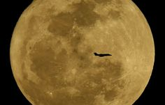 A small jet is silhouetted against the rising moon Monday, Feb. 25, in the skies above Phoenix.
