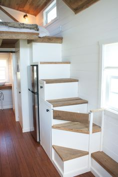 Modern farmhouse tiny house on wheels with storage stairs and reclaimed barn wood accents.