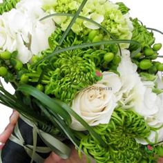 Bridal bouquet: white roses, white hydrangeas, light green hydrangeas, green spider mums and green hypericum berries. Strands of looped lily grass are crisscrossed over the top of the flowers.