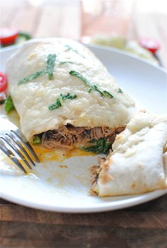 slow cooked pork burrito with black beans, gruyere cheese, avocado, cherry tomatoes, enchilada sauce, and lime...