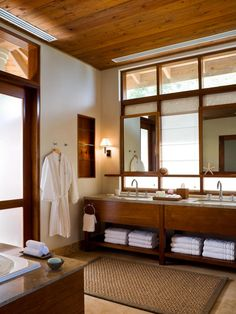 This spacious bathroom pairs a spa-like feel with the privacy of an at-home retreat. A wood plank ceiling adds a natural touch, while a double vanity provides ample room for two people to share the space. Neutral floor tiles and a woven area rug complete the look of the space.
