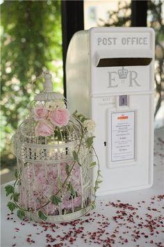 Une cage à oiseau accessoirisée de fleurs rosées pour tenir compagnie à une boite aux lettres vintage.