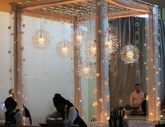 Lucite globe chandeliers are combined with glass bubbles, crystal strands and orchids, suspended from our custom silver grid on a truss structure.  Installation by Get Lit, Special Event Lighting.