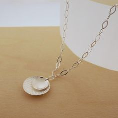 Sterling Silver necklace with a textured circle cradles a smaller circle in this modern necklace on a delicate silver chain.